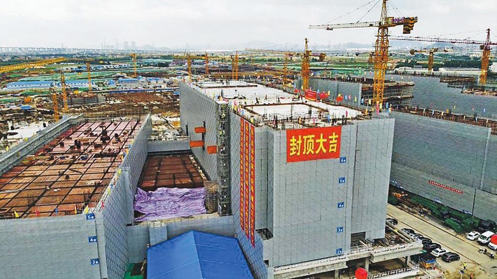 香港科技大學(廣州)的學術大樓首棟建築昨完成封頂,大樓掛上「封頂大吉」的橫額。校方預料工程可於明年3月完工,5月移交校方,9月將達到開學標準。(科大提供)