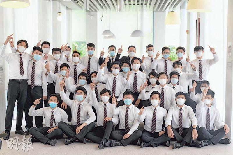 拔萃男書院今年誕17名IB狀元及12名榜眼學生,師生拍照時高舉食指,並高呼「DBS(拔萃男書院英文簡稱)」。校長鄭基恩(後排左四)表示,該校教師靈活,學生自主,是學生於新冠疫情下仍取得佳績的原因。(鍾林枝攝)