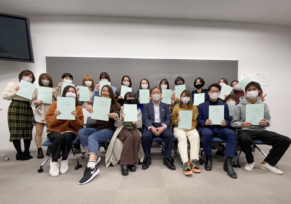 蔡易(後排左七)與武蔵野大學同學手持學習成果——畢業論文與教授合照。